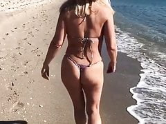 Mature cougar ambles along the beach in a panty bathing suit